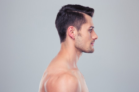 Side view portrait of a young muscular man over gray background