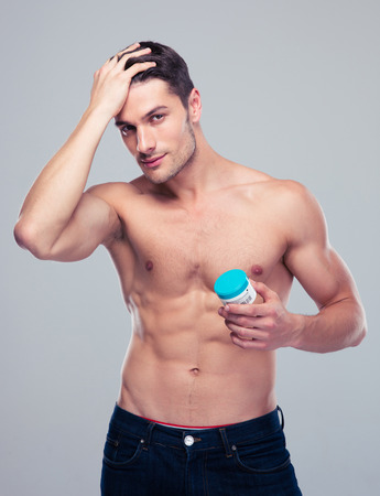 Muscular young man holding cream over gray background and looking at camera