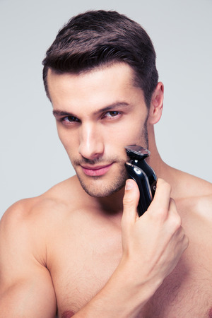 Handsome man shaving with electric razor and looking at camera over gray background