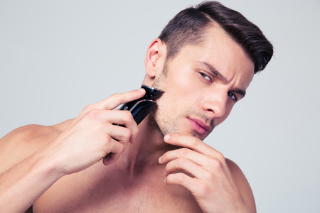 man machine: Handsome young man shaving with electric razor over gray background and looking at camera