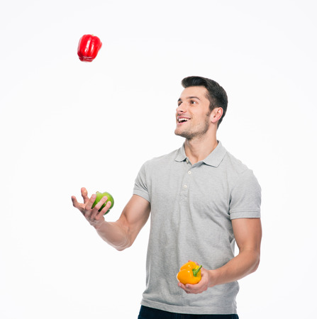 juggling: Happy young man juggling pepper isolated on a white background