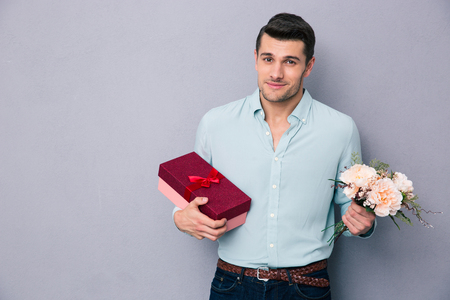 Young man holding gift box and flowers over gray background. Looking at camera