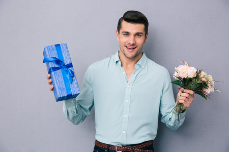 Young casual man holding gift box and flowers over gray background. Looking at camera
