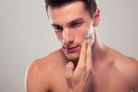 limpieza de cutis: Hombre guapo aplicar crema facial sobre fondo gris Foto de archivo