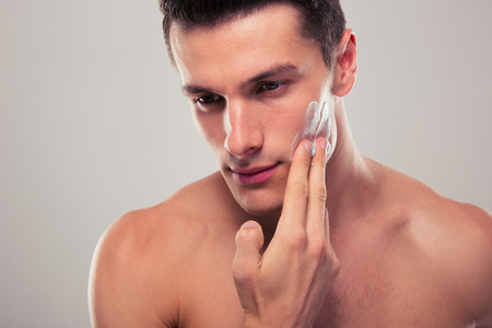 masaje facial: Hombre guapo aplicar crema facial sobre fondo gris Foto de archivo