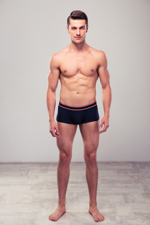 hunk: Full length portrait of a young muscular man standing in studio
