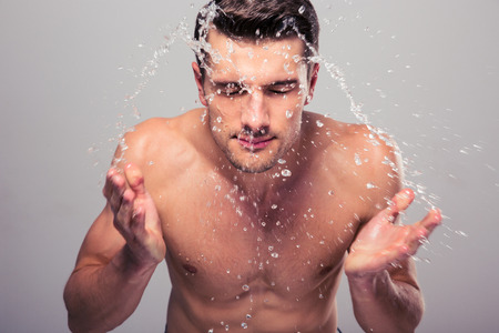 Young man spraying water on his face over gray background Stock Photo