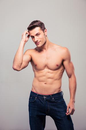 shirtless: Joven atractiva en pantalones vaqueros posando sobre fondo gris y mirando a la cámara Foto de archivo
