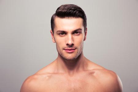 Knappe jonge man met naakt bovenlijf camera kijken op grijze achtergrond