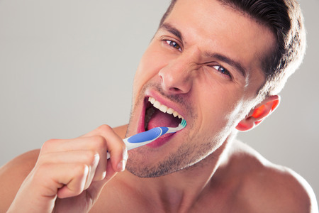Handsome man brushing teeth over gray background. Looking at camera
