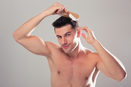 Handsome man applying hair spray to his hair over gray background. Looking at camera
