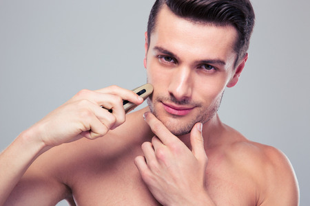concetrated: Handsome young man shaving with electric razor over gray background