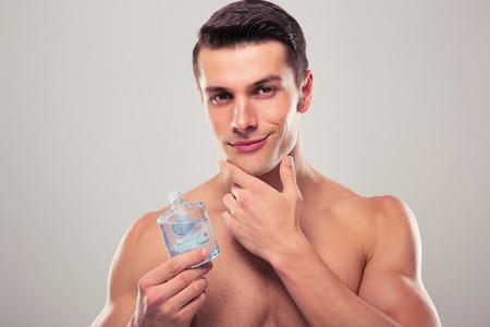 beau jeune homme: beau jeune homme appliquant une lotion après-rasage sur le visage sur fond gris