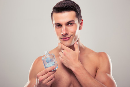staring at the camera man: handsome young man applying lotion after shave on face over gray background Stock Photo