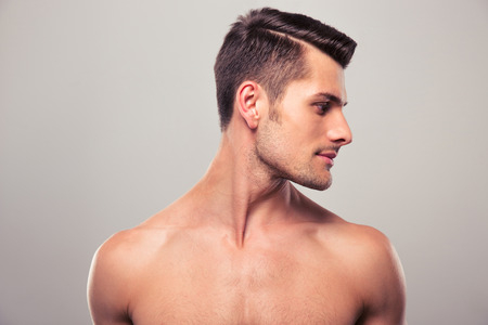Knappe jonge man weg over grijze achtergrond kijkt