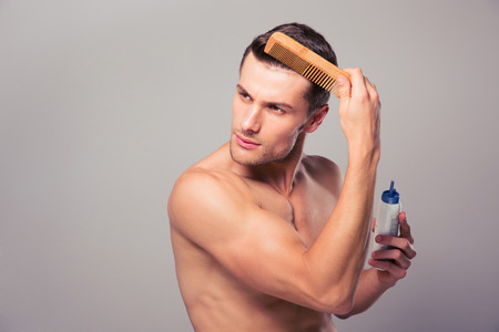 horizontal haircut: Handsome man applying hair spray to his hair over gray background. Looking away