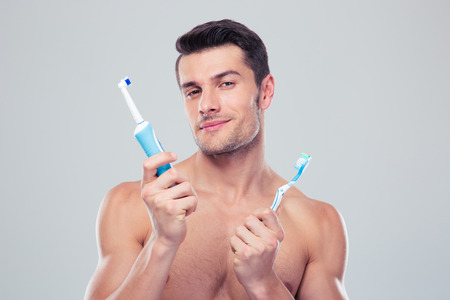 dentalcare: Young man choosing brush over gray background and looking at camera