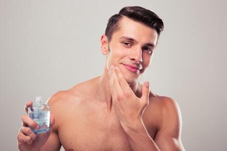 m�nner nackt: Gl�cklicher Mann Eincremen nach der Rasur auf Gesicht auf grauem Hintergrund