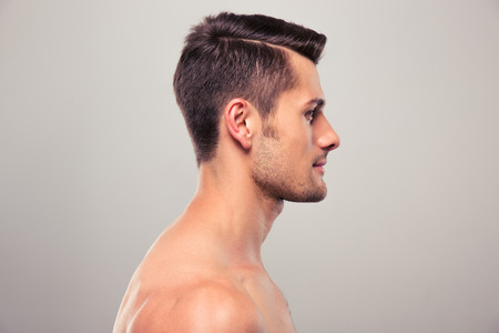 naked people: Side view portrait of a young man with nude torso over gray background Stock Photo