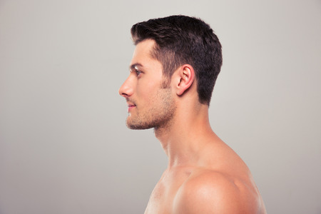 nude: Side view portrait of a young man with nude torso over gray background Stock Photo