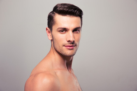 boy  naked: Confident young man looking at camera over gray background