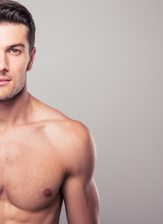 nude male body: Half body portrait of a handsome man over gray background. Looking at camera