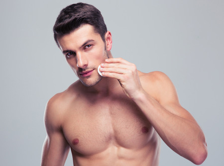 piel humana: Hombre guapo cara de la limpieza de la piel con almohadillas de algodón de bateo sobre fondo gris y mirando a cámara Foto de archivo