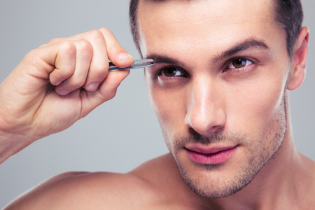 Man removing eyebrow hairs with tweezing over gray background