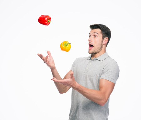 Young man juggling pepper isolated on a white background Stock Photo