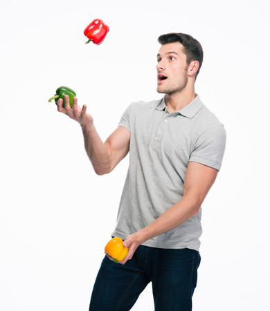 Happy young casual man juggling pepper isolated on a white background Stock Photo
