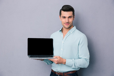 Handsome casual man showing blank laptop screen over gray background. Looking at camera photo