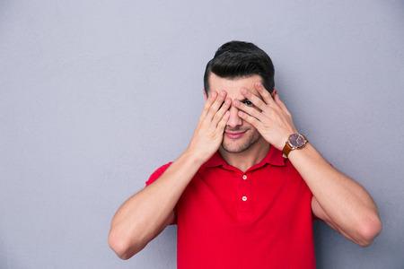 カジュアルな男の指で彼の目を覆う灰色の背景