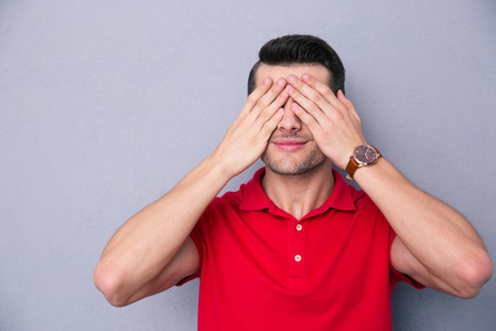blindly: Casual man covering his eyes with fingers over gray background