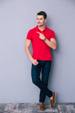 Full length portrait of a casual man pointing away and leaning on the gray wall