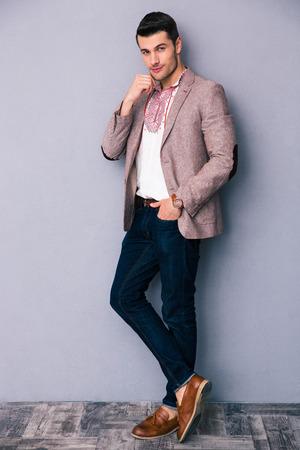 chaqueta: Retrato de cuerpo entero de un hombre de moda de pie sobre fondo gris