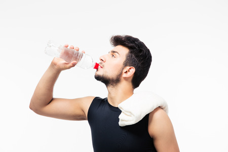man drinking water: Sports man drinking water with bottle isolated on a white background Stock Photo