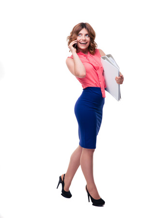 Full length portrait of a happy businesswoman talking on the phone and holding folders isolated on a white background. Looking up photo