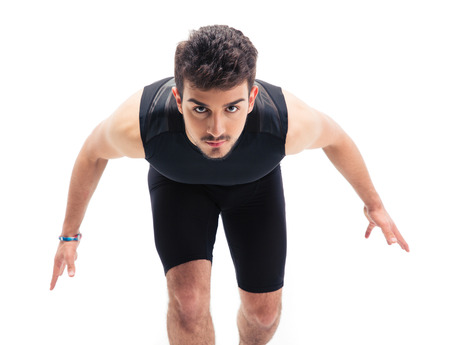 concetrated: Sports man getting ready to run isolated on a white background. Looking at camera
