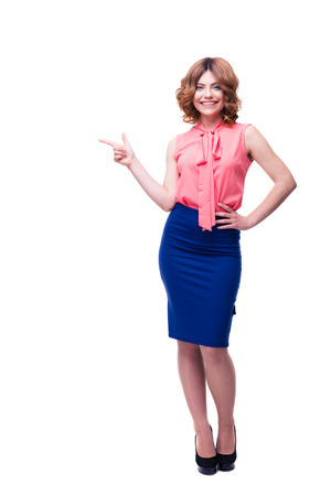 looking away from camera: Full length portrait of a smiling woman pointing finger away and looking at camera isolated on a white background