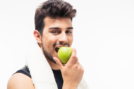 Sports man eating apple and looking at camera isolated on a white background Banque d'images