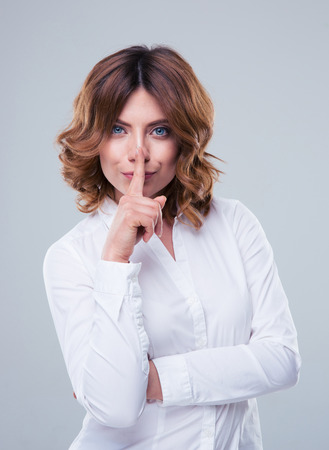 shush: Cute businesswoman showing finger over lips over gray backgorund. Be quiet! Looking at camera Stock Photo
