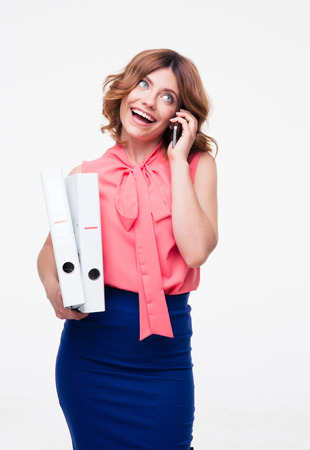 Smiling businesswoman talking on the phone and holding folders isolated on a white background. Looking up photo