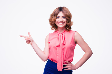 looking away from camera: Happy woman pointing finger away isolated on a white background. Looking at camera