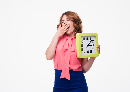 keep an eye on: Tired woman yawning and holding clock isolated on a white background