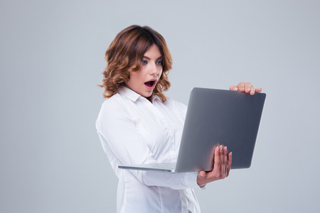 formal shirt: Surprised businesswoman standing and using laptop over gray background