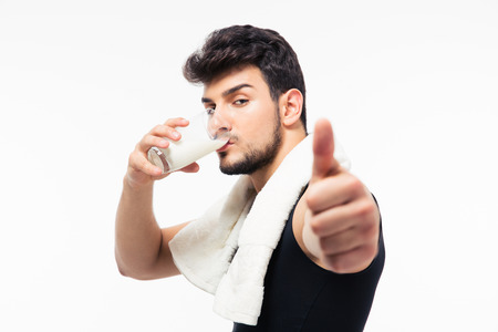 staunch: Fitness man drinking milk and showing thumb up isolated on a white background Stock Photo