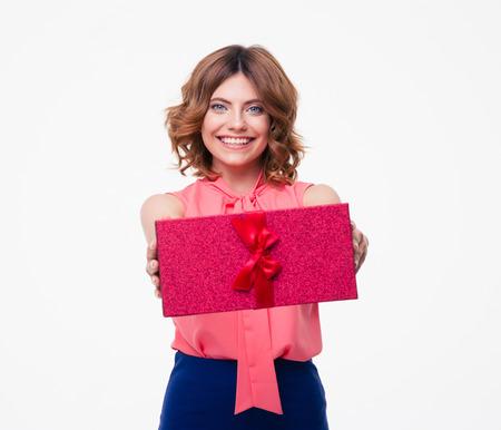 흰색 배경에 고립 된 카메라에 선물 상자를주는 행복 한 젊은 여자