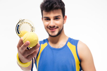 Happy sports man holding medal and tennis ball isolated on a white background. Focus on tennis ball photo