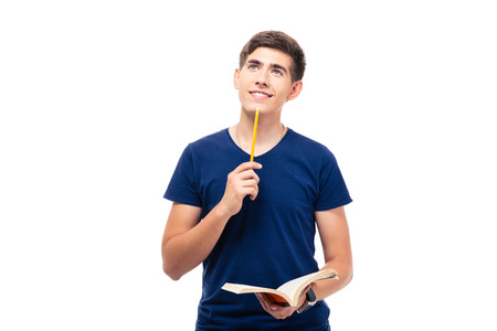 Thoughtful male student holding book and looking up isolated on a white background Foto de archivo