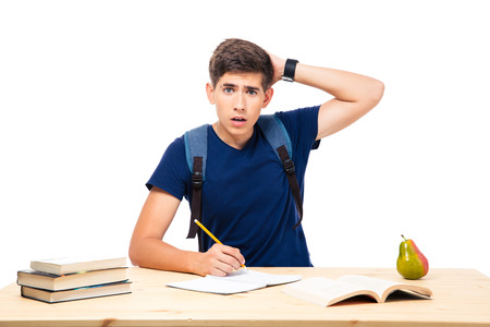 handsom: Young male student sitting at the table and writing in notebook isolated on a white background. Looking at camera
